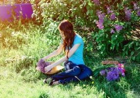young woman sitting in the park on the grass with flowers of lilac and tulips